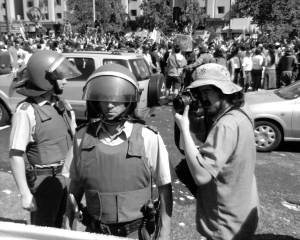 A photographer approaching police during one of the many protests against Pinochet's regime (courtesy of everystockphoto.com)