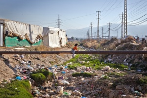 A young Syrian refugee girl slowly makes her way across a pipe over a pile of rubbish in an informal settlement in Fayda outside of Zahle, Lebanon. ©UNHCR/ S. Baldwin