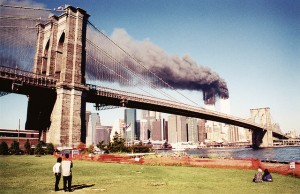 An otherwise calm New York view as the World Trade Centre towers burn in the background following the impact of two hijacked commercial airliners (courtesy of  Sean Donohue, used via Flickr creative commons licence)